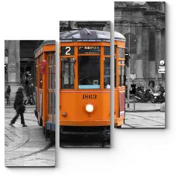 Оранжевый трамвай на сером городском фоне