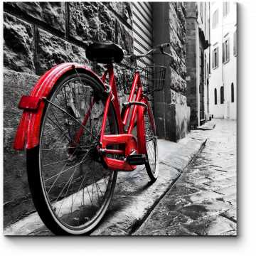Красный велосипед на мощенной улице